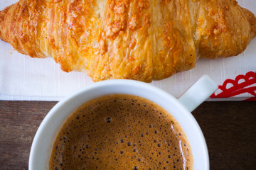Coffee cup with a croissant. Top and close view.