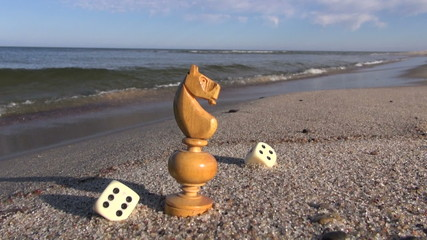 retro chess pieces and game dice on sea  beach