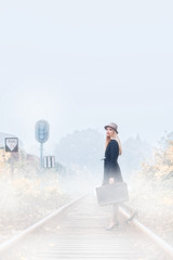 Young beautiful woman standing on train lines