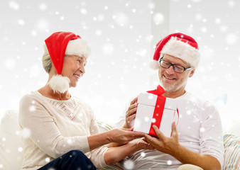 happy senior couple in santa hats with gift box