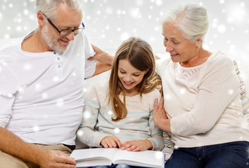 smiling family with book at home