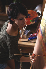 Young female painter artist in her studio.