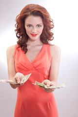 beautiful woman pink dress with dollar banknotes in the hands