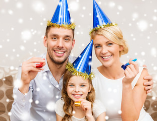 smiling family in party hats blowing favor horns