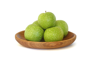 Green apples in a wooden plate isolated on white