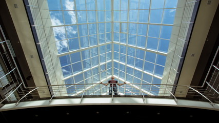Man stands on the bridge by modern attic panoramic windows