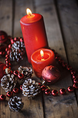 Christmas red decorations and candles on wooden table