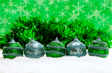 Green and silver Christmas balls, tinsel in snow and snowflakes