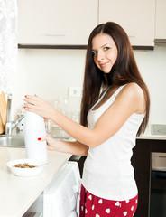 girl in  bright kitchen having breakfast