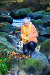 Woman alone in autumn atmosphere at the river