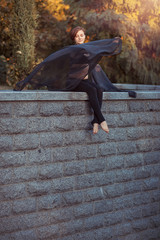 Girl dancer with black shawl sitting down on a stone wall