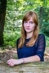 Portrait of caucasian red-haired teenage girl in forest