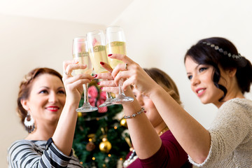 Three young women toasting with champagne