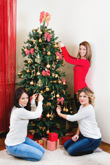 Three young women decorating a Christmas tree