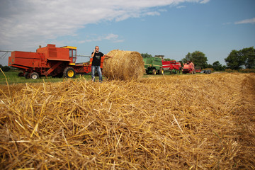 Agriculturist In A Harvested Field With Agricultural Machinery