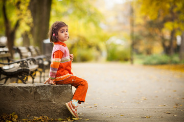 Young girl in a park sitting on a stone wall