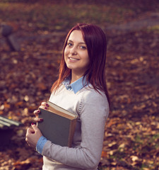 University girl in park holding a book