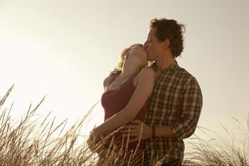Pareja de enamorados besándose entre la hierba al atardecer
