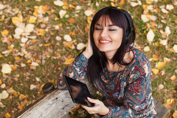 Beautiful brunette listens to the music through a digital tablet