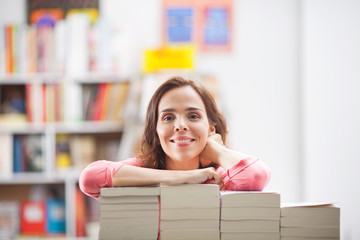 Young woman with large pile of books