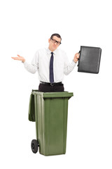 Sad man standing in a trash can