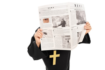 Sneaky priest peeking through a hole in newspaper