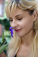 Blond female portrait smelling purple flowere with her eyes clos
