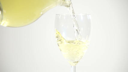 Pouring white wine on gray background