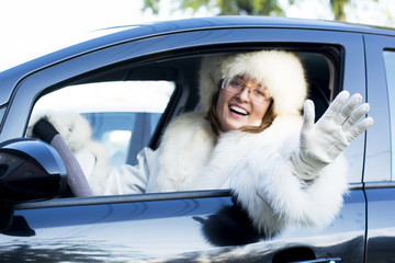 Smiling woman waving from a car window