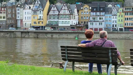 Couple on bench sitting on quay German village river, buildings