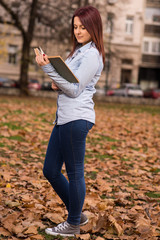 Redhead girl standing in park and reading a book