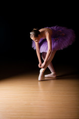 Young female ballerina adjusting her shoes