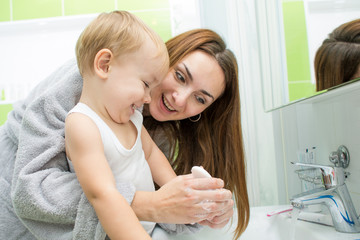 Happy mother and kid washing hands with soap in bathroom