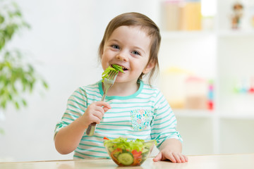kid girl eating healthy vegetables