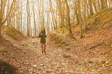 Woman walking in autumn forest