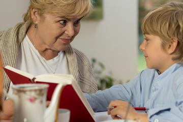 Senior babysitter caring about schoolboy