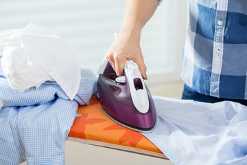 Woman ironing male shirt