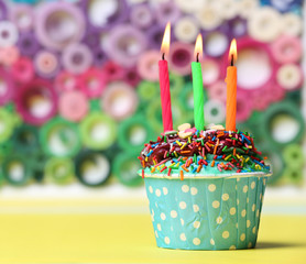 Delicious birthday cupcake on bright background