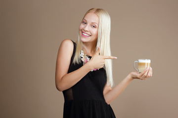 Happy Blond Woman Points Out to the Cup of Coffee