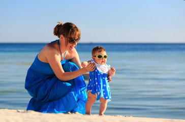 mother teaching her daughter to walk on beach