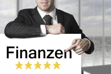 Geschäftsmann zeigt auf Schild Finanzen fünf Sterne