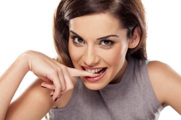 beautiful smiling girl bites her finger