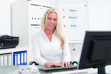 blonde businessfrau schreibt am pc