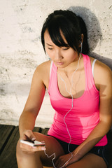 Young female athlete messagin on smartphone