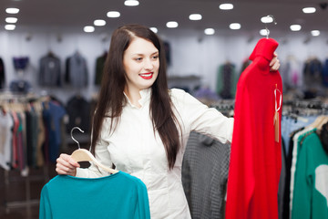 woman choosing sweater at clothing shop