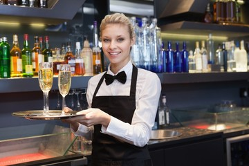 Pretty waitress holding a tray of champagne