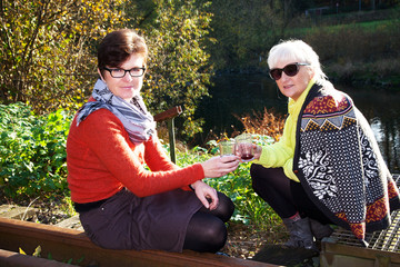 Two women with a glass of red wine in nature