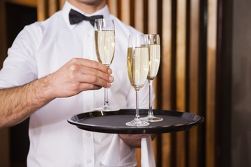 Waiter holding tray of champagne