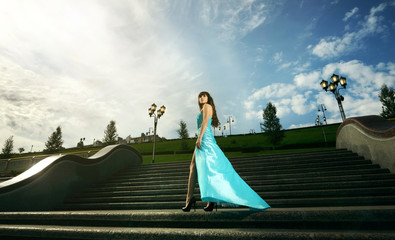 Attractive girl in long evening dress. black background