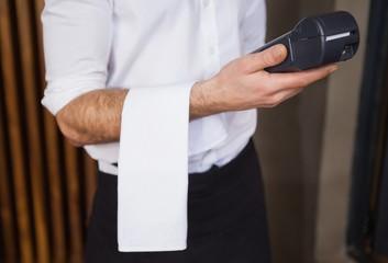 Handsome waiter holding credit card machine